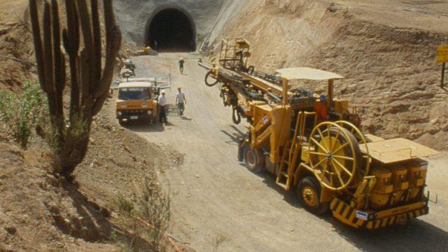 maquinaria trabajando en un camino a la entrada de un tunel