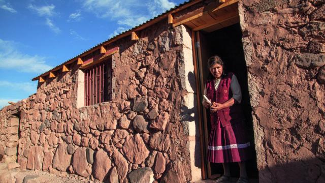 mujer en la puerta de su casa de piedras en una zona desértica, pueblos originarios