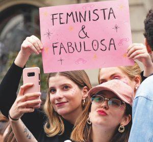 """en la fotografía dos mujeres, una sostiene un letrero que dice """"feminista y orgullos"""" y otra se toma una selfie"""