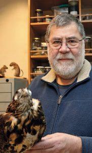 fotografía de Fabián Jaksic sosteniendo un ave