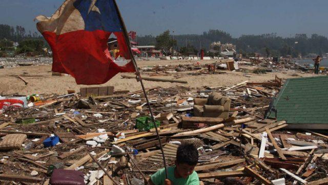niño sostiene una bandera chilena dota y en el fondo ruinas de casas derrumbadas por un terremoto