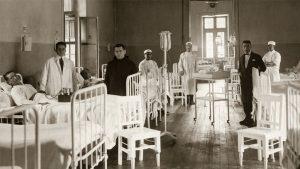 fotografía antigua de una sala de hospital correspondiente a la antigua Casa de Orates parecen en ella doctores y pacientes en camillas