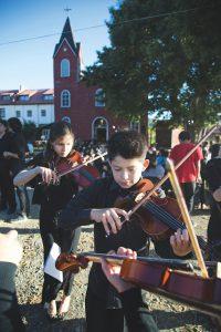 niños tocando violines al fondo una iglesia