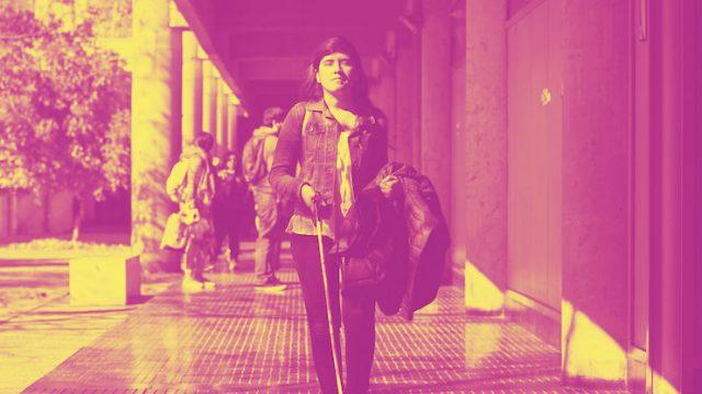 mujer en Situación de Discapacidad caminando por el campus san joaquín de la UC