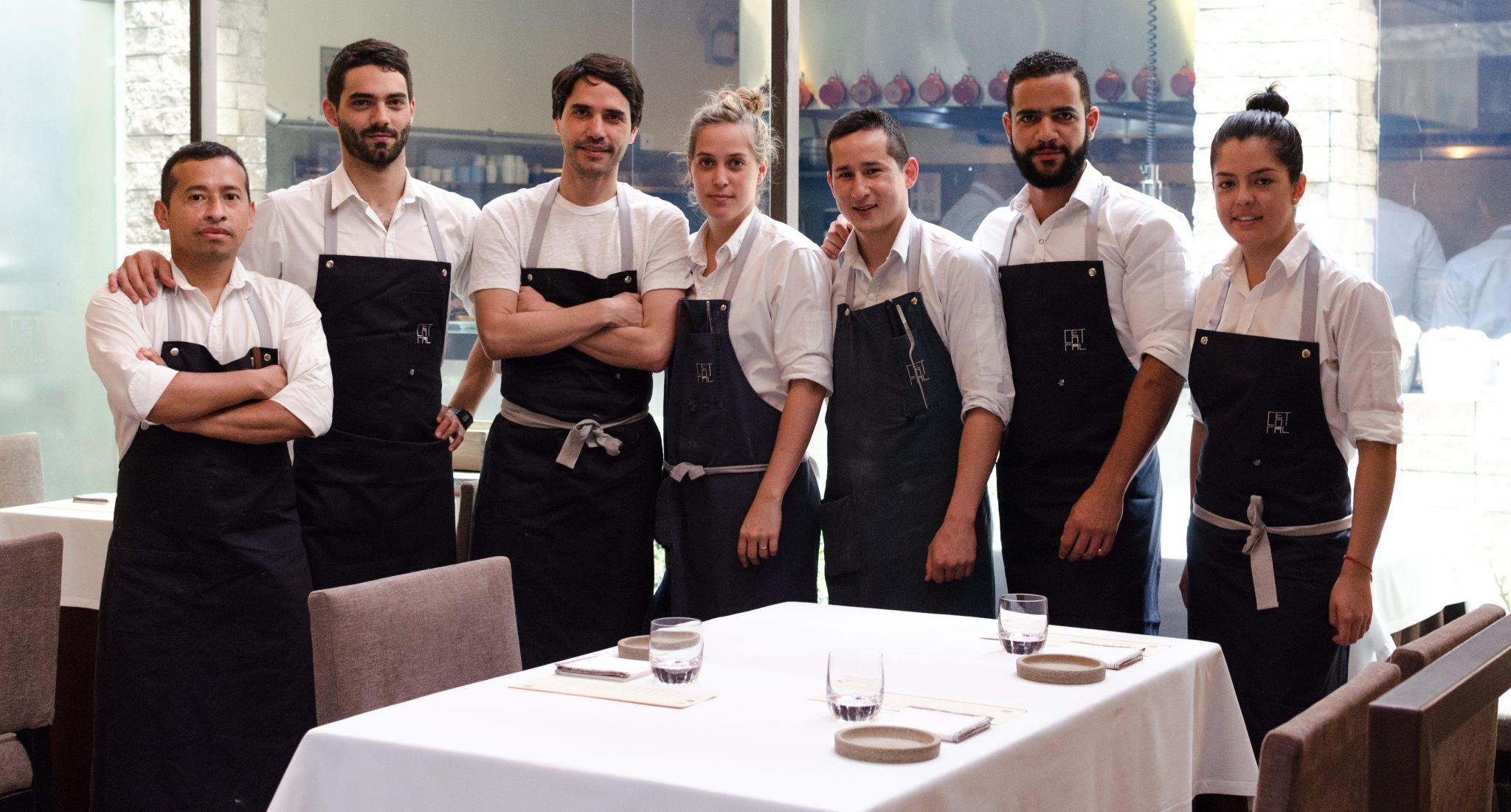 en la fotografía siete garzones con delantal negro en un restaurant peruano