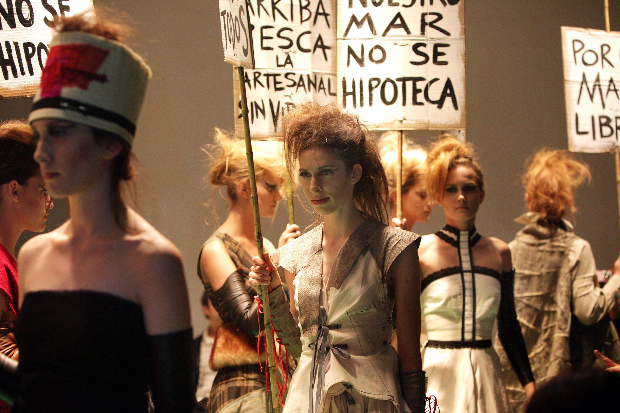 personas en un desfile de moda portando carteles