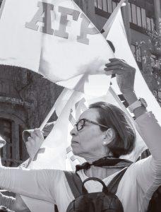 Mujer en una marcha sosteniendo una bandera que dice No más AFP