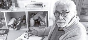 hombre adulto mayor sentado pintando con pincel un dibujo