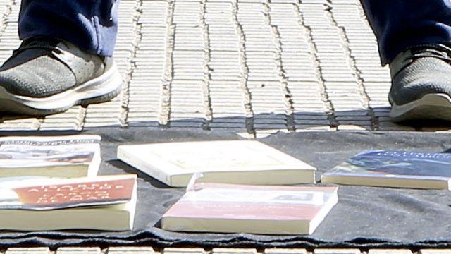 pies de una persona vendiendo libros en la calle, transgrediendo la propiedad intelectual