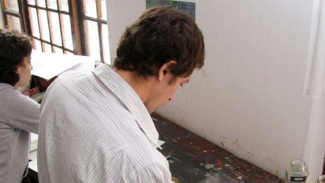 personas en un taller de pintura, rol de las universidades