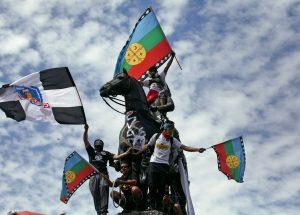 En la fotografía personas arriba del monumento a Baquedano y portan banderas mapuche