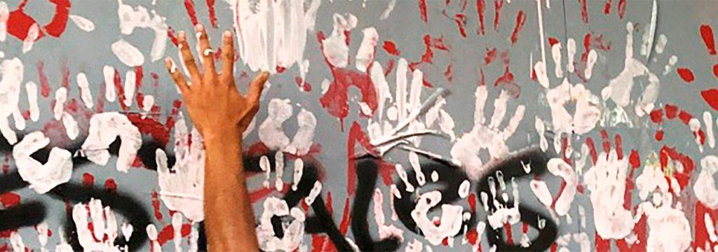 una mano sobre una pared pintadas con manos