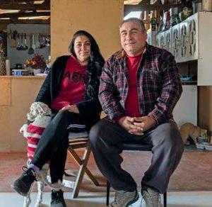 Fotografía de Pamela Rojas con su pareja en el living de su casa